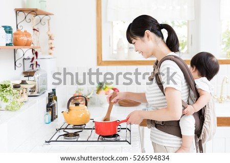 portrait of asian mother and baby in the kitchen