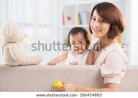 Portrait of Asian mother and daughter sitting on the sofa looking at the camera