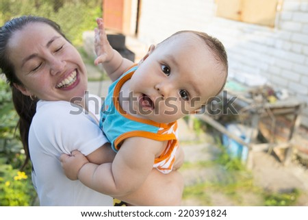 Portrait of Asian mother holding crazy baby on hands on summer sunny garden background Empty copy space for inscription - stock photo