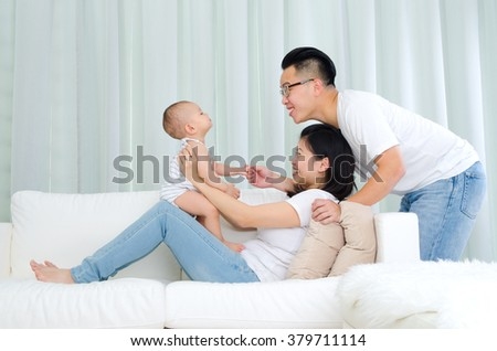 Portrait of asian parent playing with their baby - stock photo