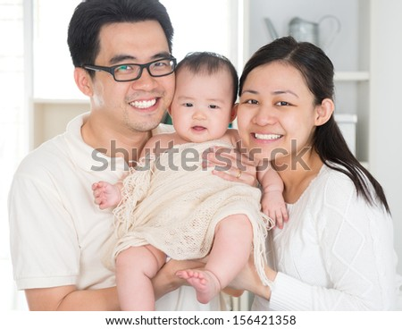 Portrait of Asian parents and six months old baby girl at home. Asian family. - stock photo