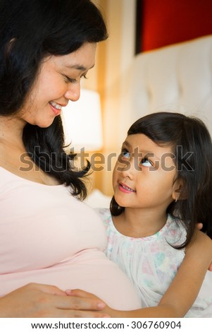portrait of asian pregnant mother educate pregnancy to daughter  - stock photo