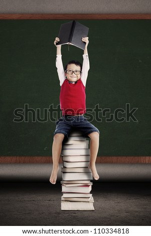 Portrait of asian schoolboy holding a book and sitting on a stack of books in front of blackboard - stock photo