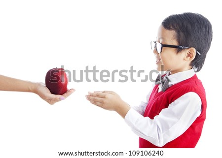 Portrait of asian schoolchild receiving a red apple from his mother. shot in studio isolated on white - stock photo