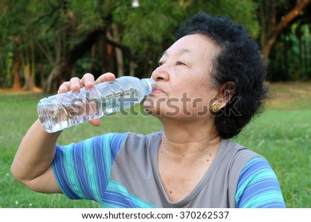 Portrait of Asian Senior drinking water