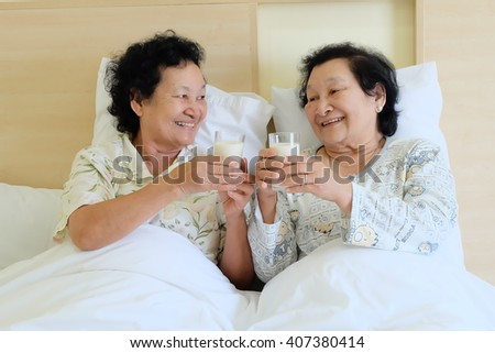 Portrait of Asian senior woman drinking milk on bed