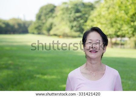 Portrait of Asian senior woman in the park - stock photo
