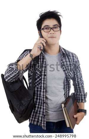 Portrait of asian student talking on the phone, isolated over white background - stock photo