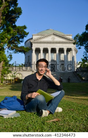 Portrait of asian student use use of the cellphone sitting a grass at a campus