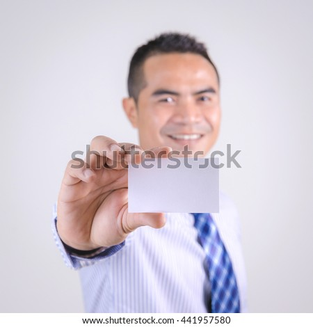 Portrait of asian Thai business man smile and showing blank white business card selective focus shallow depth of field - stock photo