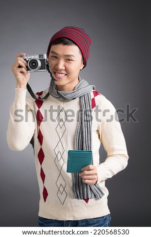 Portrait of Asian tourist in warm clothes with passport and camera - stock photo