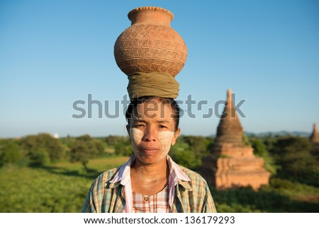 Portrait of Asian traditional farmer carrying clay pot on head going back home, Bagan, Myanmar