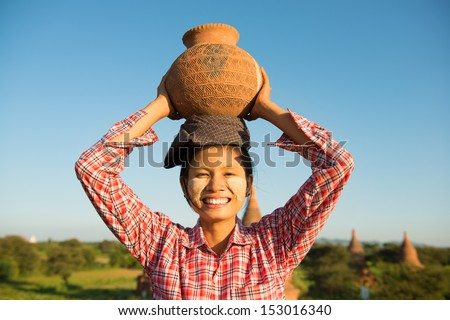 Portrait of Asian traditional female farmer carrying clay pot on head going back home, Bagan, Myanmar - stock photo