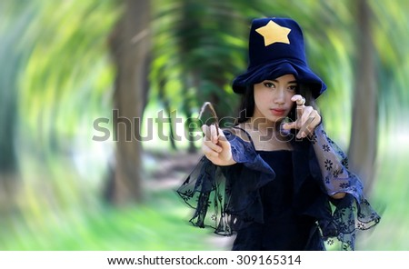 portrait of Asian witchy woman on black dress and holding twig in garden - stock photo