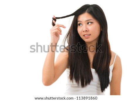 Portrait of Asian woman holding damaged dry hair and sad looking isolated on white background