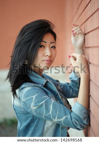 Portrait of asian woman near the wall - stock photo
