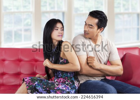 Portrait of asian woman quarreling with her boyfriend and elbowed him - stock photo