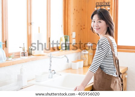 portrait of asian woman relaxing in the kitchen