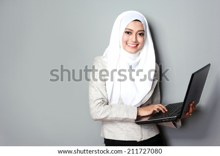 portrait of asian woman smiling while using laptop computer - stock photo
