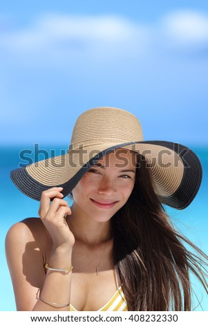 Portrait of Asian woman with beach hat smiling happy wearing fashion straw hat for skin care sun protection. Face skincare beauty. Beautiful mixed race young adult girl on summer vacation travel. - stock photo