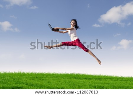 Portrait of asian woman with laptop jumping in meadow expressing her success - stock photo
