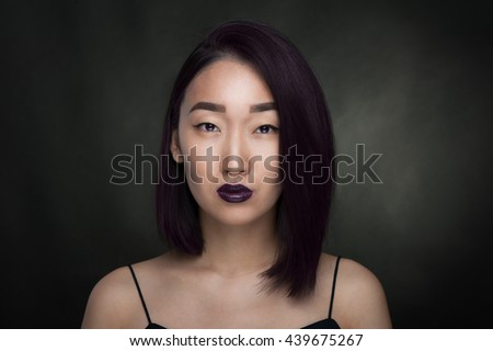 Portrait of asian woman with violet hair on black background