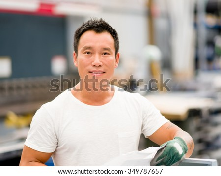 portrait of asian worker in production plant working on the factory floor