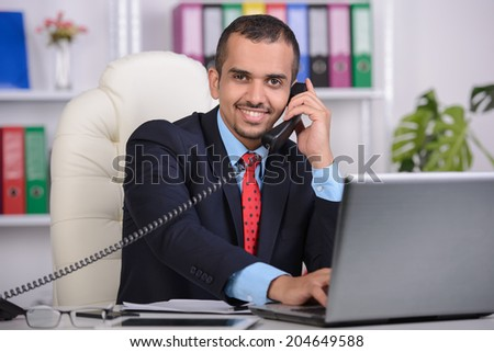 Portrait of Asian young businessman, talking on phone, using laptop, sitting in office