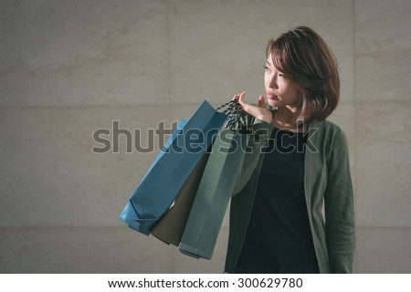 Portrait of Asian young girl carrying shopping bags and looking aside