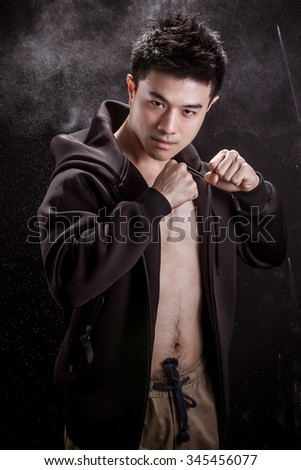 Portrait of Asian young man on black background - Fitness healthy guy and fighter concpet