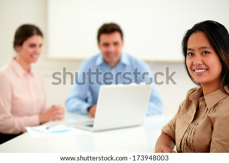 Portrait of asiatic businesswoman looking and smiling at you while sitting and working with male and female coworker on office