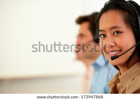 Portrait of asiatic operator woman with microphone smiling at you while sitting on workplace - copyspace