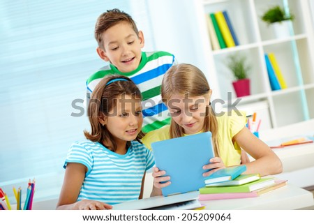 Portrait of astonished classmates at workplace using digital tablet - stock photo