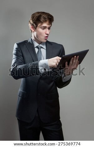 Portrait of astonished young businessman with touch screen computer, on gray background