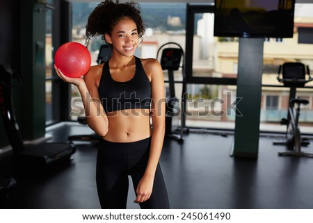 Portrait of athletic afro american woman holding little stability ball at fitness class in health center - stock photo