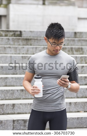 Portrait of athletic Chinese man resting after urban run through city streets. Asian male runner taking break standing relaxing. - stock photo