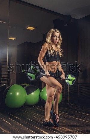 Portrait of athletic female with barbell in a gym club.