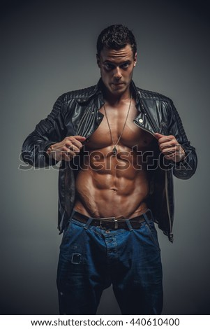 Portrait of athletic male in a jeans and leather jacket on a grey background. - stock photo