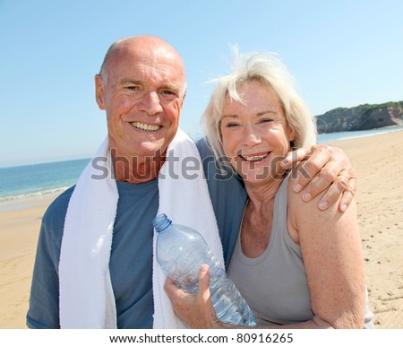 Portrait of athletic senior couple on the beach - stock photo
