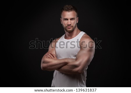 Portrait of athletic young man wearing undershirt isolated on black background