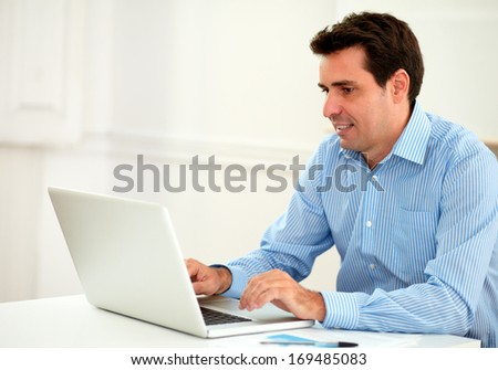 Portrait of attractive adult businessman on blue shirt using his laptop while sitting on office desk