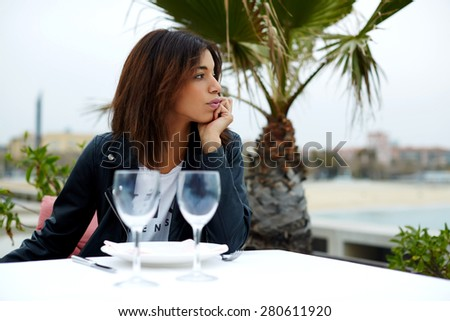Portrait of attractive afro american woman enjoying a good day in restaurant while sitting at the table, charming female hipster sitting on the terrace of sidewalk cafe with palm tree on background - stock photo