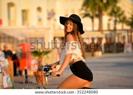 Portrait of attractive amazed brunette with open mouth wearing black hat and white top. Sexy girl having fun riding her bicycle along embankment  - stock photo