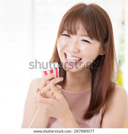 Portrait of attractive Asian girl eating cupcake and laughing. Young woman indoors living lifestyle at home.