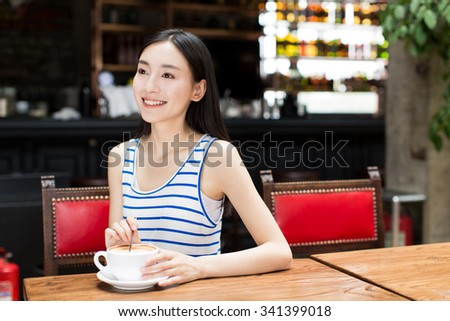 portrait of attractive asian girl enjoying cup of hot coffee in the morning. - stock photo