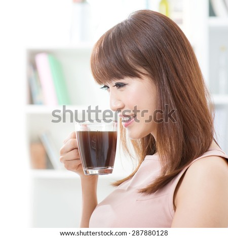 Portrait of attractive Asian girl enjoying cup of hot coffee in the morning. Young woman indoors living lifestyle at home. - stock photo