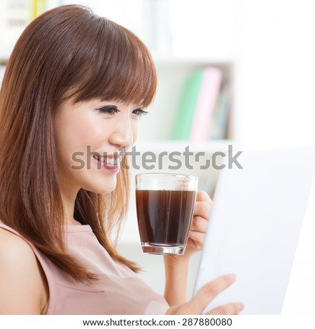 Portrait of attractive Asian girl enjoying cup of hot coffee while using computer tablet in the morning. Young woman indoors living lifestyle at home.