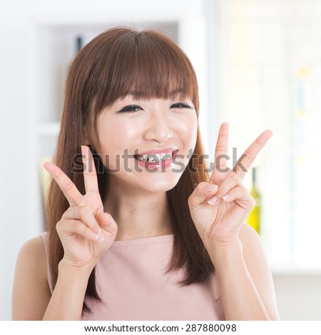 Portrait of attractive Asian girl showing peace or v hand sign. Young woman indoors living lifestyle at home. - stock photo