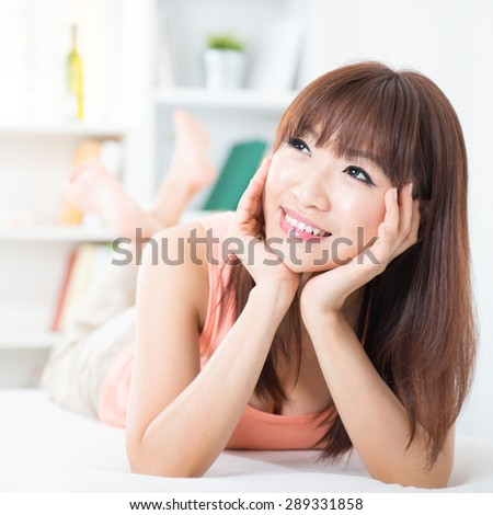 Portrait of attractive Asian girl smiling and daydreaming on bed. Young woman indoors living lifestyle at home.