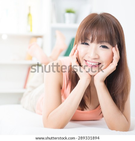 Portrait of attractive Asian girl smiling and resting on bed. Young woman indoors living lifestyle at home. - stock photo